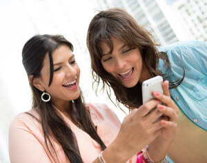 Women texting on a cell phone looking very happy